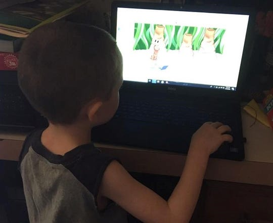 Landric Feighner, a first-grade student at Battleground Elementary School, works on completing an online assignment from his West Lafayette home. Feighner has been participating in e-learning since the school closed due to COVID.