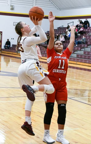 Berne Union senior Emily Blevins shoots the ball as Fairfield Christian's Jenna Grabans during their Mid-State League-Cardinal Division game Tuesday night. Berne Union won 80-34.