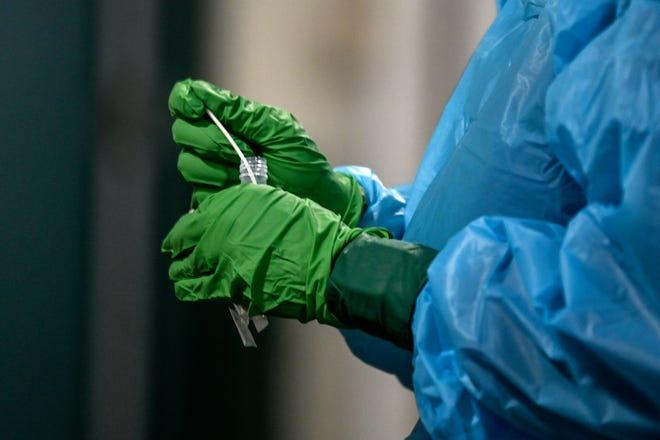 Employee Joan Sirigiri prepares a COVID-19 test specimen at the COVID-19 testing site at Spartan Stadium on Wednesday, Nov. 25, 2020, in East Lansing.