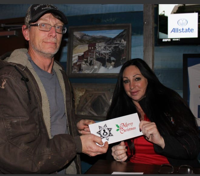 Toot's diner Richard Moss gives a donation for Shop with the Sheriff to Amee Smith of the Sheriff's Citizens Academy Alumni Association during the 2019 fund-raiser at Toot's.