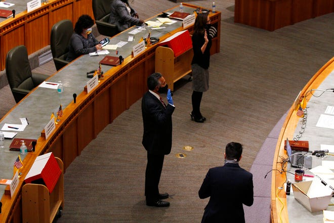 Reps. Art De La Cruz, with blue glove, and Tara Lujan are sworn in at a special session of the state legislature Tuesday, Nov. 24, 2020, in Santa Fe, N.M. The legislature considered a virus relief package Tuesday. (AP Photo/Cedar Attanasio)