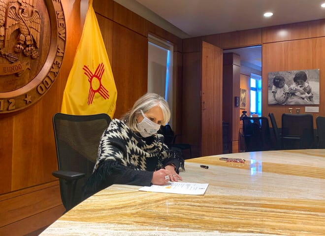 In this photo provided by the New Mexico Office of the Governor, Gov. Michelle Lujan Grisham signs a $330 million economic relief package aimed at helping small businesses and out-of-work New Mexicans while at the State Capitol, Wednesday, Nov. 25, 2020 in Santa Fe, N.M.