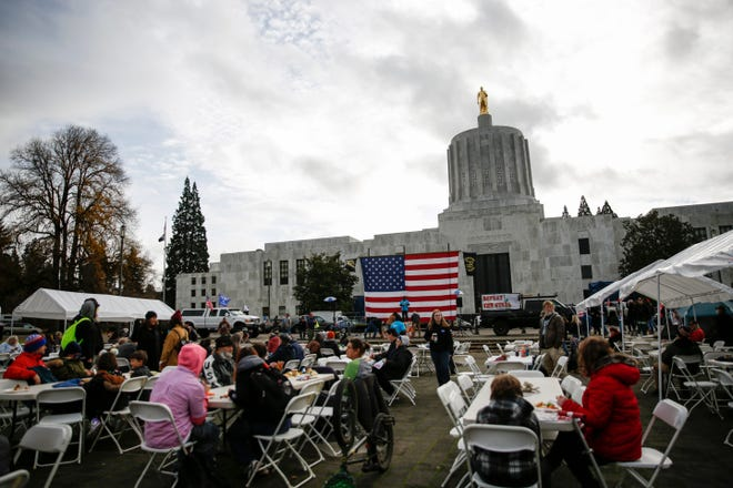 People gather in protest of the presidential election results and to defy COVID-19 restrictions on Wednesday, Nov. 25, 2020 at the Oregon State Capitol. The protest included a potluck-style Thanksgiving meal.