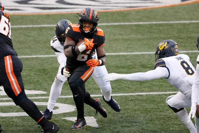 Oregon State Beavers running back Jermar Jefferson (6) carries the ball as California Golden Bears linebacker Kuony Deng (8) and defensive end Zeandae Johnson (44) defend during the first half at Reser Stadium on Nov 21, 2020.