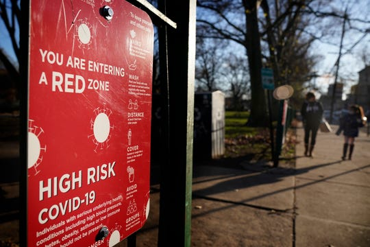 A sign at the entrance to a park on Tuesday warns pedestrians about increased risk for the coronavirus in the Ironbound section of Newark, N.J.