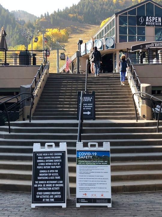 In this Oct. 3, 2020, photo, visitors climb the stairs past COVID-19 safety signs to the gondola at Aspen Mountain in Aspen, Colorado.