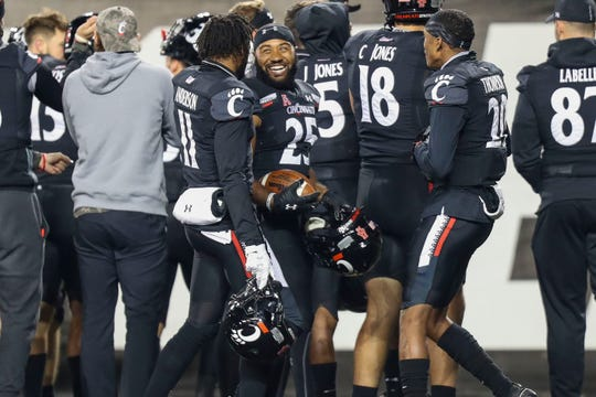 Cincinnati cornerback Sammy Anderson (11) celebrates with running back Cameron Young (25) after the team's defeat of East Carolina at Nippert Stadium.