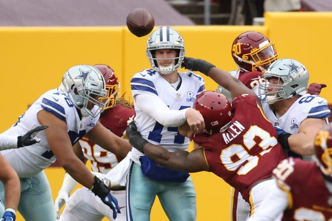 El mariscal de campo de los Dallas Cowboys Andy Dalton (14) pasa el balón bajo la presión del tackle defensivo del equipo de fútbol de Washington Jonathan Allen (93) en el segundo trimestre en el FedEx Field.