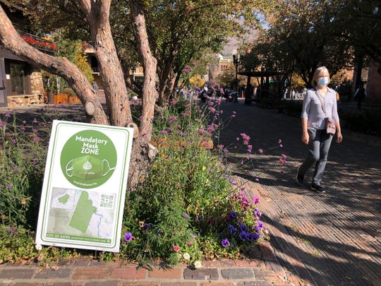 In this Oct. 3, 2020, photo, a pedestrian walks past one of the many signs along the mandatory mask zone in the downtown area in Aspen, Colorado.