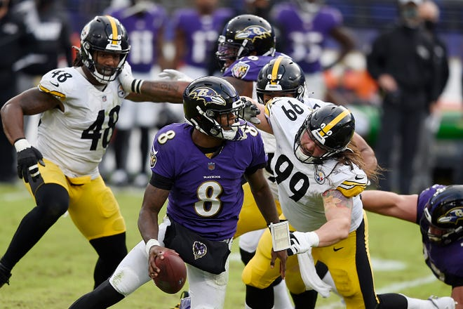Baltimore Ravens quarterback Lamar Jackson tries to avoid a Steelers rush in their Nov. 1 game in Baltimore. The Ravens-Steelers' second matchup of the season was postponed until Wednesday.