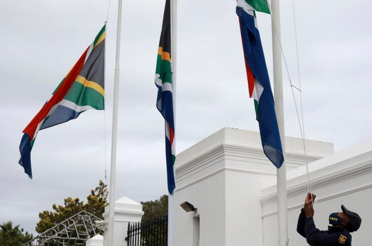 A policeman adjusts South African flags to half-mast outside parliament in Cape Town, South Africa, Wednesday, Nov. 25, 2020. South Africa declared five days of mourning starting today to remember those who have lost their lives to COVID-19 and gender-based violence.