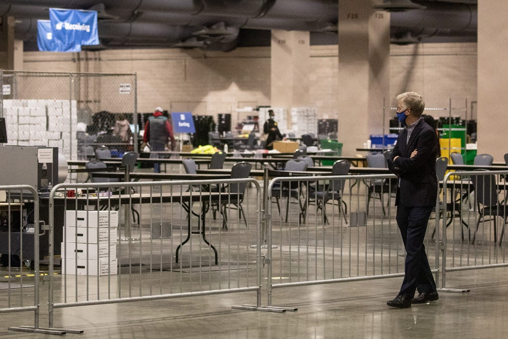 A man watches from the observers' area as election workers count ballots at the Philadelphia Convention Center on Nov. 6, 2020.