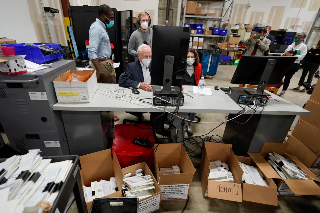 Democratic and Republican representatives review absentee ballots at the Fulton County Elections Preparation Center in Atlanta on Wednesday, Nov. 4, 2020.