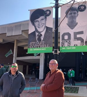 """WQBQ Sports Director Billy Matthews, right, visited the graceful Memorial Fountain that stands in front of the campus entrance to Marshall University's Memorial Student Center. It was designed to reaffirm """"purposeful life"""" as much as mourn """"tragic loss"""" after the deaths of the 75 football players, coaches and fans who died in the tragic crash of Nov. 14, 1970."""
