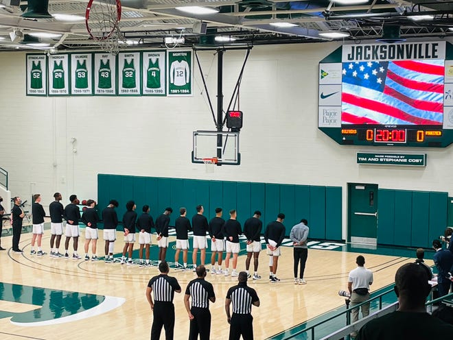 Jacksonville University players and staff stand for the National Anthem before Wednesday's opening basketball game of the season at Swisher Gym.