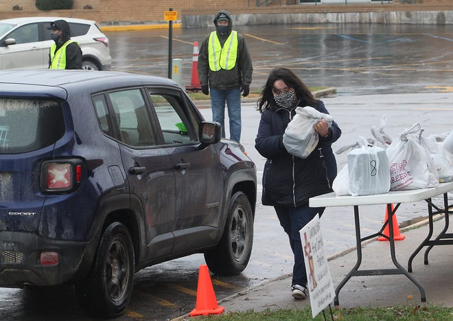 Crystal Wright prepares to place Thanksgiving meals into a vehicle Wednesday during the 16th annual Moberly Community Goodwill Thanksgiving Dinner. Meals were distributed in a drive-thru or pedestrian pick-up at Saint Pius X Catholic Church instead of the sit-down meal at Zion Lutheran Church in Moberly due to COVID-19 restrictions.