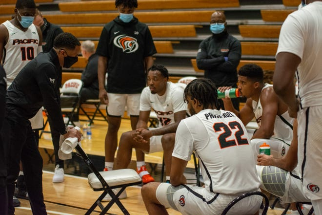 Pacific men's basketball coach Damon Stoudamire, left, speaks to his team during the season opener against UC Riverside.