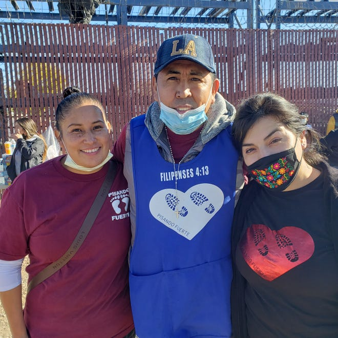 Victoria Giron, left, her husband Ruben Giron, center, and Maria Mariano prepared food and provided clothing along with their group of friends on Thanksgiving Day in downtown Stockton.