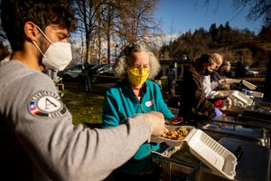 Jan Zoll and Giovanni Rivera assemble Thanksgiving dinner to-go for people at Washington Jefferson Park on Thursday.