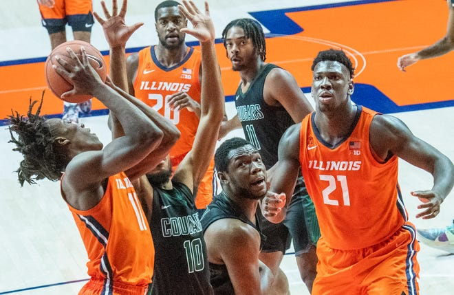 Illinois guard Ayo Dosunmu (11) shoots as Chicago State's forward Carlo Marble (10) defends during the second half of an NCAA college basketball game in Champaign, Ill., Thursday, Nov. 26, 2020. (Robin Scholz/The News-Gazette via AP)