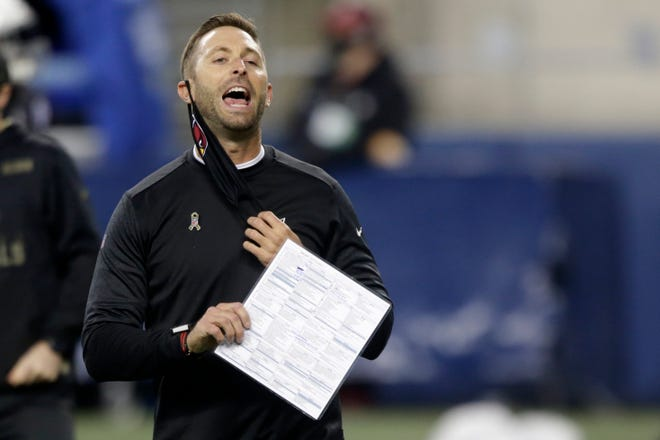 Arizona head coach Kliff Kingsbury removes his mask to yell before an NFL football game against Seattle.