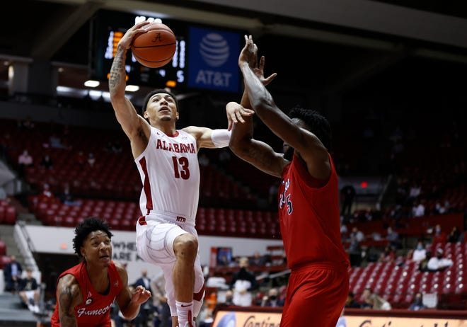Alabama guard Jahvon Quinerly (13) goes to the basket against Jacksonville State forward Amanze Negumezi (5) during the opening game of the season in Coleman Coliseum. [University of Alabama Photo by Kent Gidley]