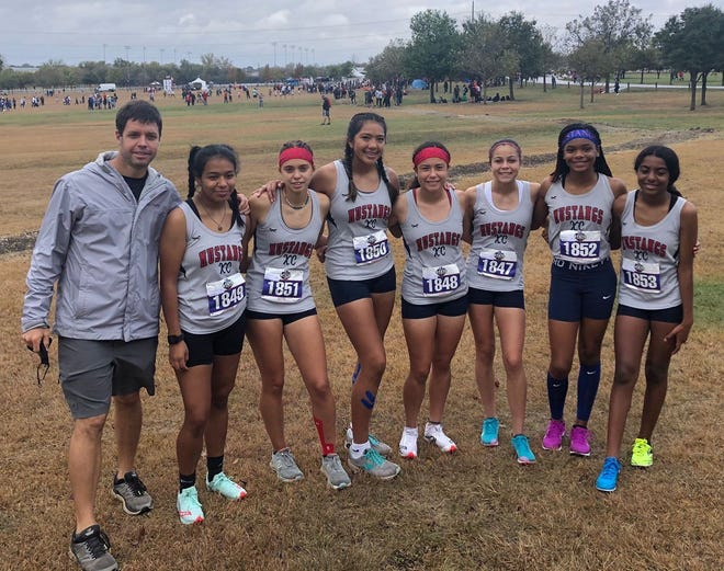 Life Waxahachie's girls cross country team poses with head coach Daniel Dagen (left) at the University Interscholastic League state championships at Old Settlers Park in Round Rock.