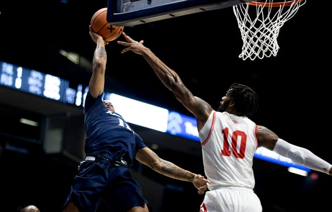 Xavier Musketeers guard Dwon Odom (11) hits as layup over Bradley Braves forward Elijah Childs (10) putting Xavier up 51-50 with less than 10 seconds left in the game in the second half of the NCAA men's basketball game on Thursday, Nov. 26, 2020, in Cincinnati.