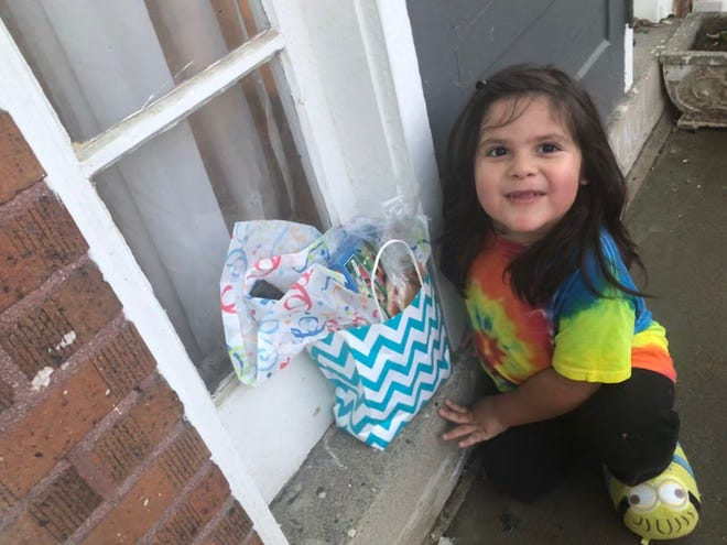 Bonnie Jean Feldkamp's son Ezra finds a gift bag on their front porch from a kind neighbor. Neighbors leave gift bags for Feldkamp knowing she stays isolated during this pandemic due to health concerns.