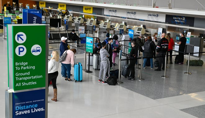 Travelers wait to check in for a flight at Detroit Metro Airport North Terminal on Thanksgiving Day in 2020.