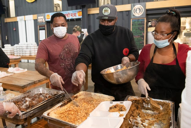 Chef Max Hardy, center, of COOP Caribbean Fusion restaurant inside the Detroit Shipping Company, works with volunteer George Tinnon, left, and COOP manager Alexis Fox, right, to prepare and package up Thanksgiving meals for the needy inside the Detroit Shipping Company on Thanksgiving Day.
