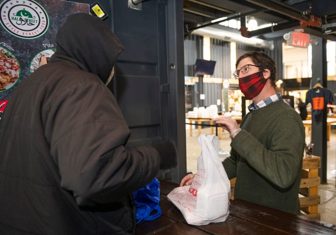 Jon Hartzell, one of the owners of Detroit Shipping Company, hands a chef-prepared Thanksgiving meal to-go to a needy person at Detroit Shipping Company on Thanksgiving Day.