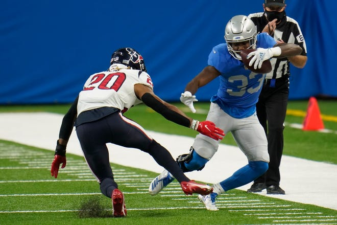 Detroit Lions yang berlari kembali Kerryon Johnson mencoba melewati keselamatan Houston Texas, Justin Reid.