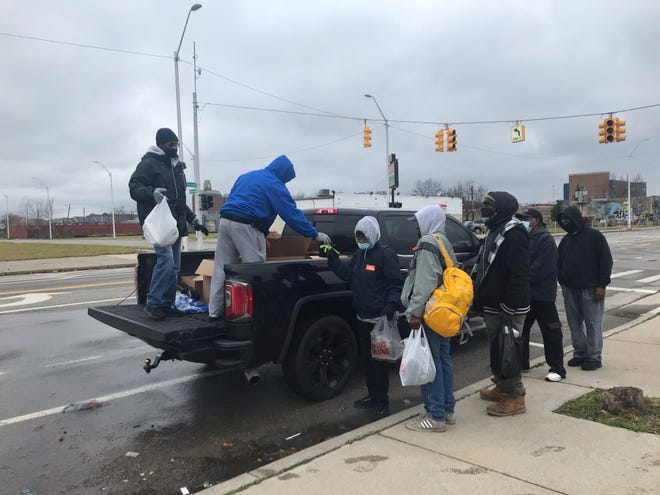 Cleveland Evans, left, and Eric L. Johnson, right, hand out homecooked Thanksgiving meals at Peterboro and Second in Detroit.