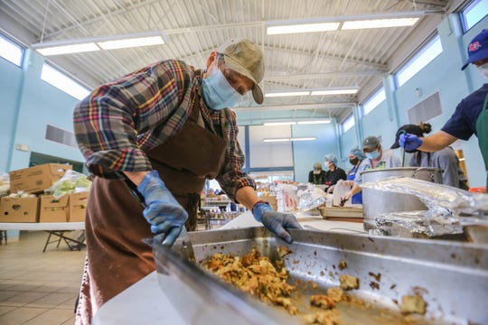 Wearing a face mask and gloves because of the COVID-19 pandemic, Jan Archey serves Thanksgiving meals to those in need at El Caldito Soup Kitchen in Las Cruces on Thursday, Nov. 26, 2020.