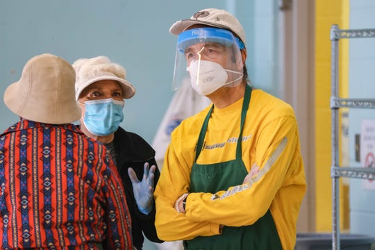 Wearing personal protective equipment, Norman Duttweiler helps make Thanksgiving meals for those in need at El Caldito Soup Kitchen in Las Cruces on Thursday, Nov. 26, 2020.
