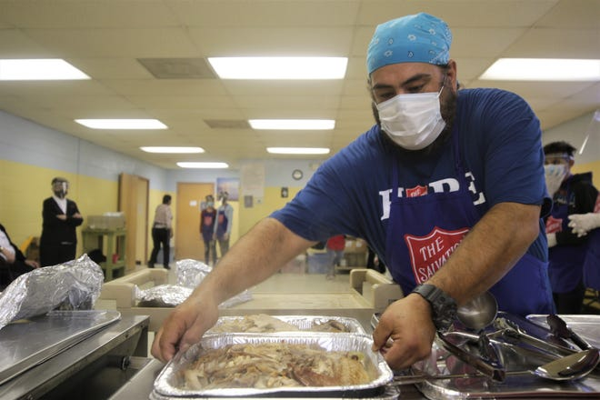 Cook Elijah Miera places a tray of turkey out to help to serve Thanksgiving to-go meals at Daily Bread on Nov. 26, at 405 S. Behrend Ave. in Farmington.
