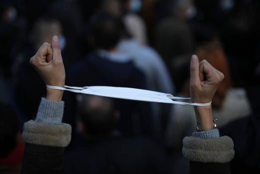 A demonstrator has her mask around her cuffs as restaurants, bars and night clubs owners demonstrate in Marseille, southern France, Thursday Nov.26, 2020. The government laid out details Thursday of a gradual easing of France's monthlong virus lockdown, including hundreds of millions of euros in new aid for struggling workers and students and businesses forced to close.