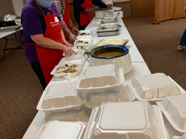 Patty Johnson, left, Larry Koenigseker and Ivory Lyons, right, help prepare turkey dinners Thursday at First Christian Church. The effort was part of Christ United Methodist Church's annual Thanksgiving effort.