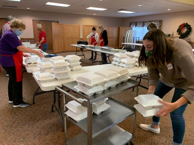 Allison Launcher stacks up turkey dinners ready to be distributed Thursday at First Christian Church in Alliance. The church this year joined the long-running Thanksgiving meal effort of Christ United Methodist Church.