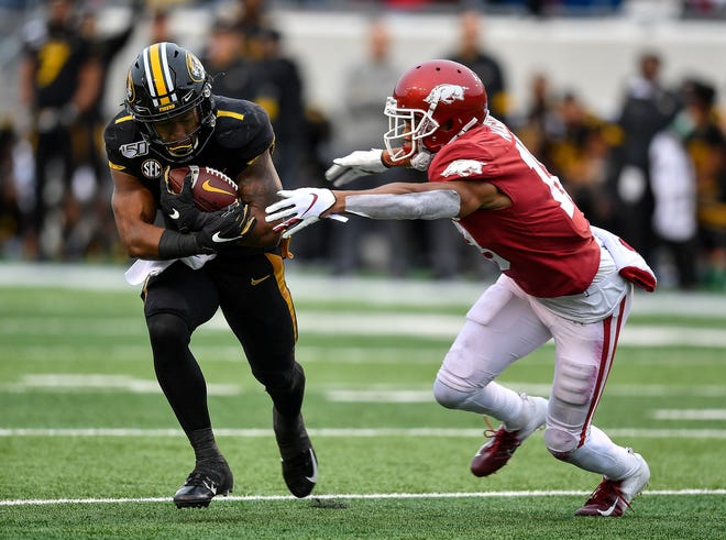 Missouri running back Tyler Badie, left, tries to evade an Arkansas defender during a game Nov. 27, 2019, at War Memorial Stadium in Little Rock, Ark.