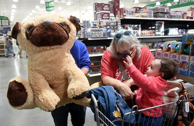 Laura Reddick watches her granddaughter, Ellie Lincoln, 1, reach for a large stuffed animal held by her uncle, Tanner Reddick, on Friday while Christmas shopping at Menards.