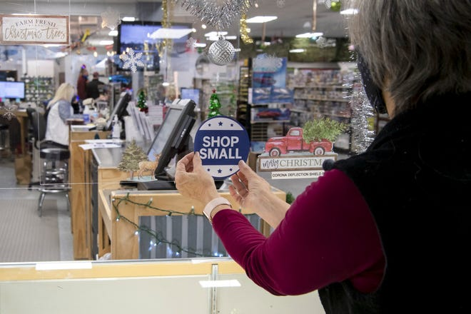 "Smoke Stack Hobby Shop co-owner Patti Riordan places a ""Shop Local"" sign on a plexiglass divider as the shop prepares for Small Business Saturday in Lancaster."