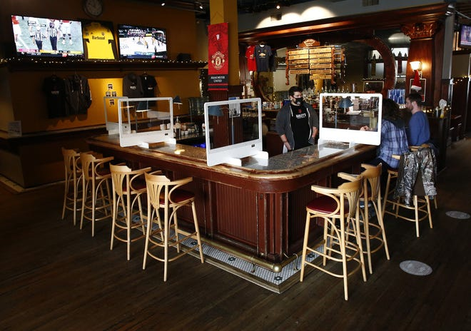 Businesses that rely on events at Nationwide Arena and the Greater Columbus Convention Center are struggling. Bartender Brendon Fabian, left, talks with customers Chyanne Lindaman and Craig Padleckas on a slow afternoon at Barley's Brewing Company on Friday.