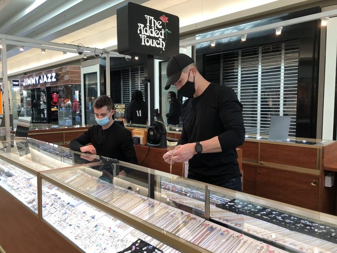 Andrew Pack (right) and his younger brother, Caleb, staff the jewelry kiosk they operate in the Eastland Mall on Black Friday. Their family has run the business at the mall since 1988, and Andrew said that despite the pandemic, business has been surprisingly good.