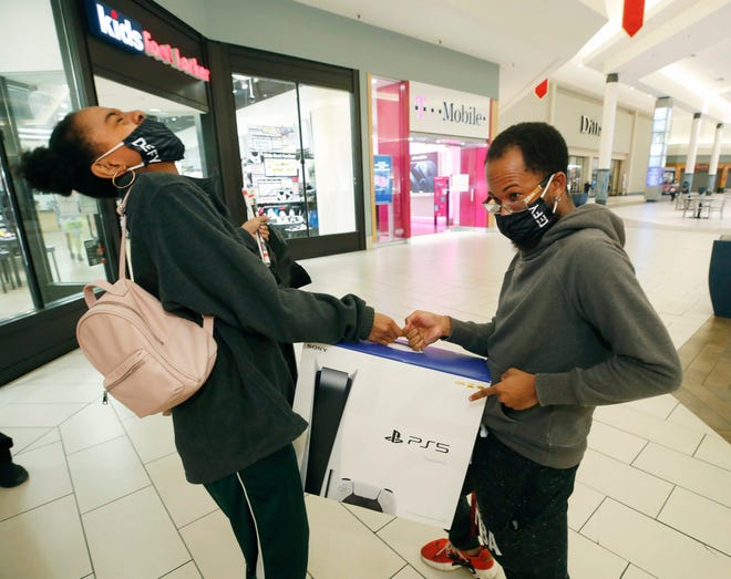 Jazmon Parham and Desi Lyons celebrate their purchase of a PlayStation 5 from Game Stop in Daytona Beach, Fla., while Black Friday shopping. Getting a new video game system this holiday season? Make sure to avoid injuries.