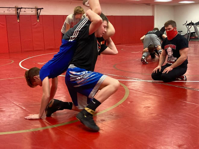 General McLane wrestling coach Ryan Cook, right, watches lightweights Christian Gillette, top, and Ben Watkins, bottom, spar during Friday's practice. Cook is required to wear a facial covering as part of the school's COVID-19 protocols, but the school is not requiring the wrestlers to wear them while they compete.