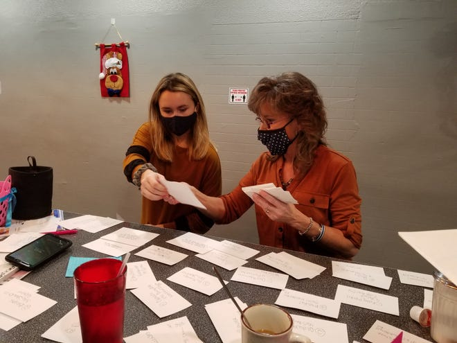 Victoria (left) and Lori Cramp of Billy Schu's restaurant sort address cards for deliveries of the restaurant's free Thanksgiving dinner.