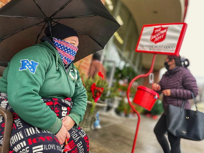 Mekalanne Matter of Galesburg, left, shelters under an umbrella as she rings the bell for the Salvation Army at Hy-Vee, 2030 E. Main St., on Wednesday, Nov. 25, 2020.