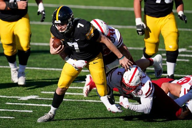 Iowa quarterback Spencer Petras (7) is tackled by Nebraska linebacker Caleb Tannor (2) and linebacker Garrett Nelson (44) during the first half of Friday's game in Iowa City, Iowa. (AP Photo/Charlie Neibergall)